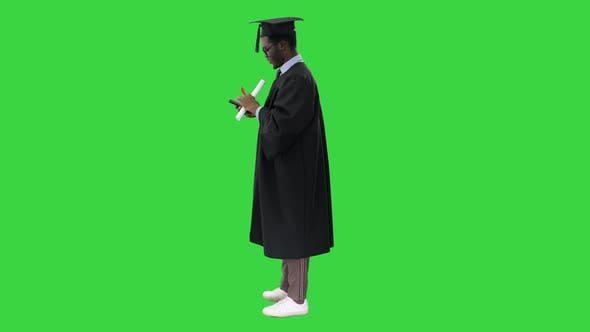 Happy African American Male Student in Graduation Robe Taking Phone Selfies with His Diploma on a