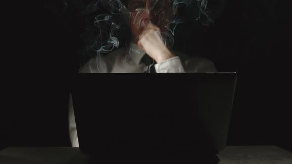 Businessman Is Thinking At The Smoking Laptop