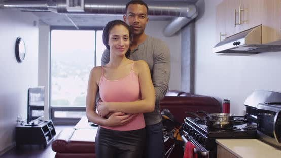 Thumbnail for Portrait of happy Black and Hispanic couple looking at camera standing in apartment