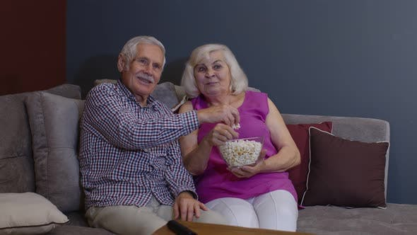 Thumbnail for Portrait of Elderly Couple Watching TV at Home Eating Popcorn Enjoying Film Together at Home