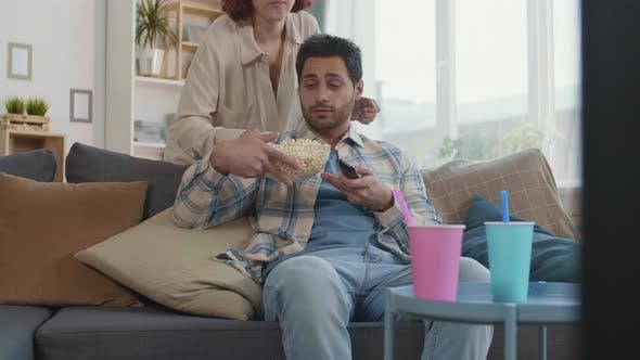 Petite amie apportant du pop-corn à son petit ami