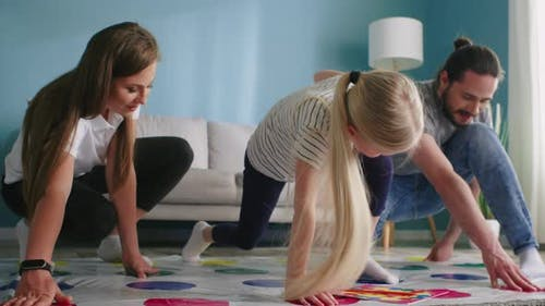 Parents and Small Daughter Play Twister