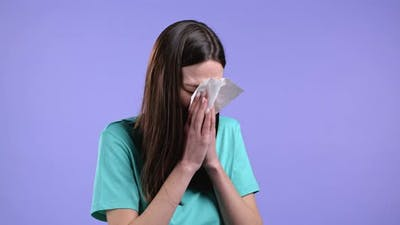 Young Woman Sneezes Into Tissue