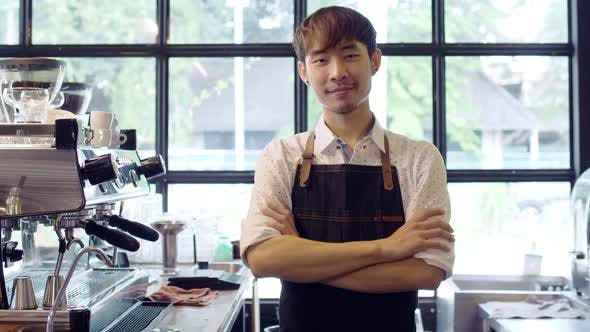 Portrait of young workers at cafe in uniform with apron.
