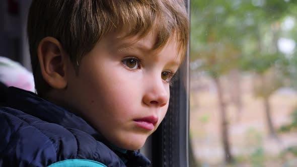 Thumbnail for Trauriger junger Passagier. Nahaufnahme Aufnahme eines kleinen neugierigen Jungen Blick aus dem Fenster in Zug