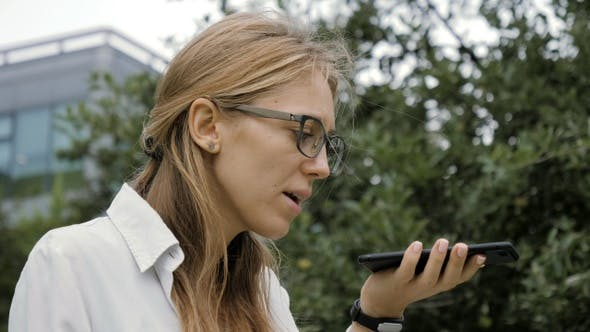 Thumbnail for Woman Wearing Glasses Using a Smart Phone Voice Recognition