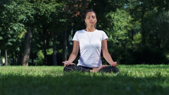 Thumbnail for Girl Doing Yoga in the Park and Listening Music on Headphones