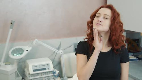 Dreamy Woman Who Gently Touches Her Face After the Procedure of Skin Restoration and Rejuvenation in