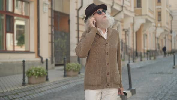 Thumbnail for Portrait of Cheerful Old Man with Long Grey Hair and Beard Talking on the Phone While Walking with