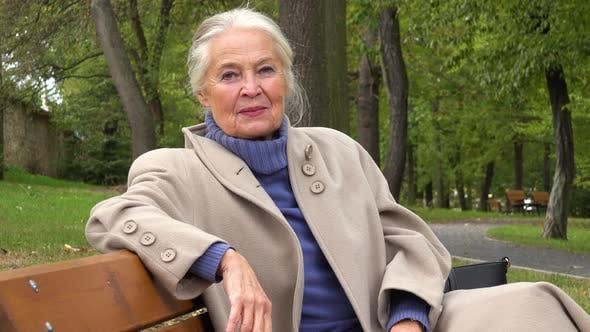 Thumbnail for An Elderly Woman Sits on a Bench in a Park and Smiles at the Camera