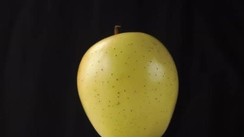 Gros plan pomme verte mûre sur un fond de papier froissé foncé.