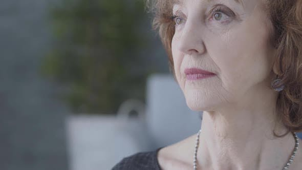 Thumbnail for Close Up Portrait of a Senior Mature Woman Looking Away in the Foreground. The Blurred Figure of the