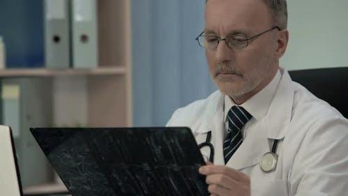Traumatologist Looking at X-Ray, Diagnosing Vertebra Weakness in Patient's Neck
