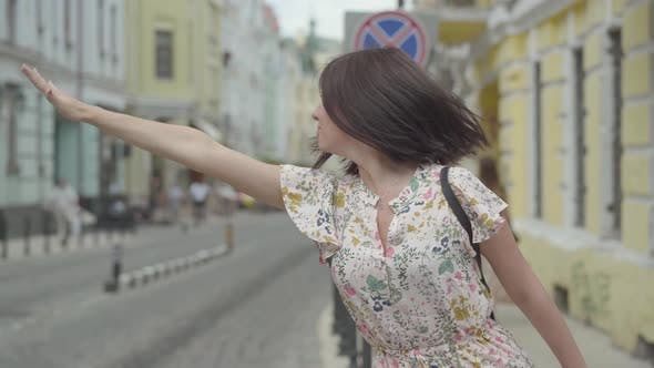Thumbnail for Pretty Carefree Young Woman Wearing Summer Dress with Shopping Bags in Hands Trying To Catch a Taxi
