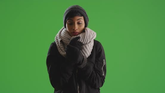 Thumbnail for Black female wearing beanie and gloves standing in cold weather on green screen