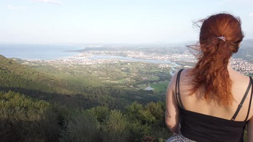 young woman watching the views from the top of the mountain