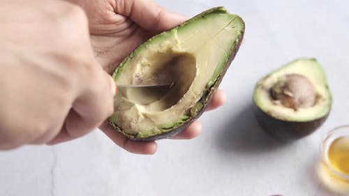 Women Hand Cutting Slice of Avocado with Knife
