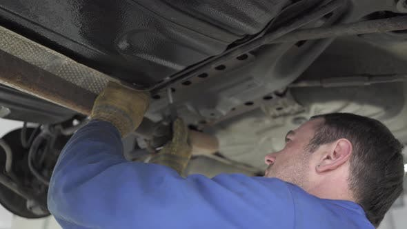 Thumbnail for Experienced Auto Mechanic in a Blue Uniform Standing Under the Car with a Wrench and Tightening the