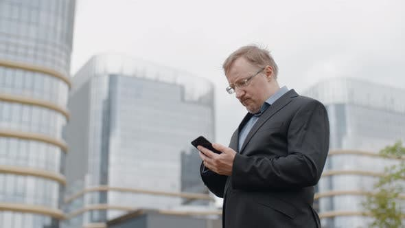 Thumbnail for Man Texting on Smartphone, Adult Manager or Businessman Have Difficulties Using Mobile Device