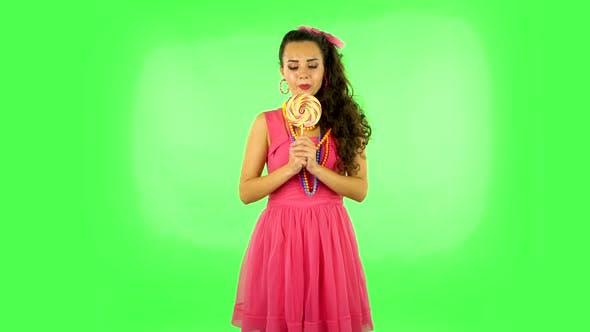 Thumbnail for Mädchen mit großer Freude isst eine große bunte Süßigkeiten beim Genießen. Grüner Bildschirm
