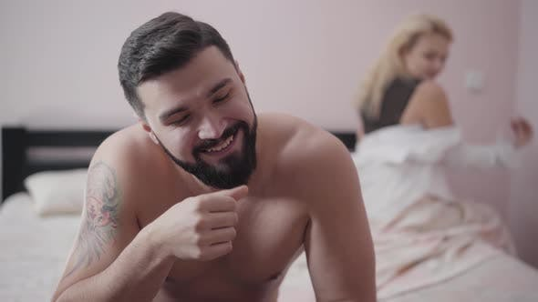 Thumbnail for Close-up Face of Satisfied Caucasian Man with Tattoo on Shoulder Sitting on Bed. Young Blond Woman