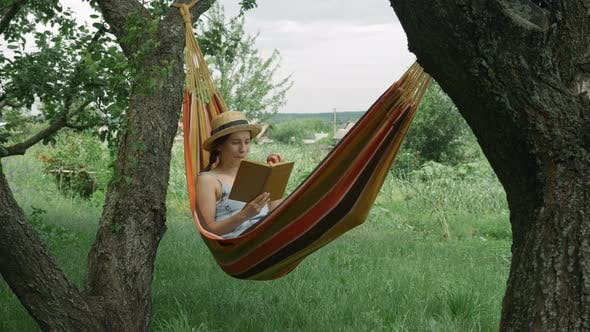Female relaxing in hammock at green garden reading book and eating an apple
