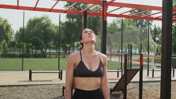 Young Athletic Woman in Sports Black Top and Leggings Going in for Sports Doing a Pullup in an