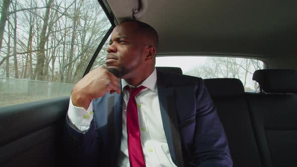 Pensive Businessman Riding in Car Backseat and Looking Out Window
