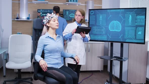 Female Patient Sitting on a Chair with Brainwaves Sensors