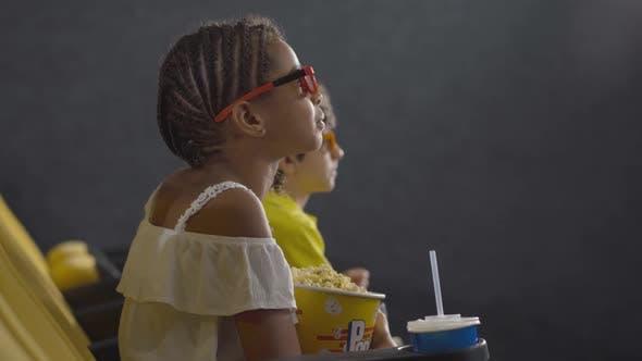 Seitenansicht von Little Girl beobachten 3D Film im Kino mit verschwommenen Kindern im Hintergrund