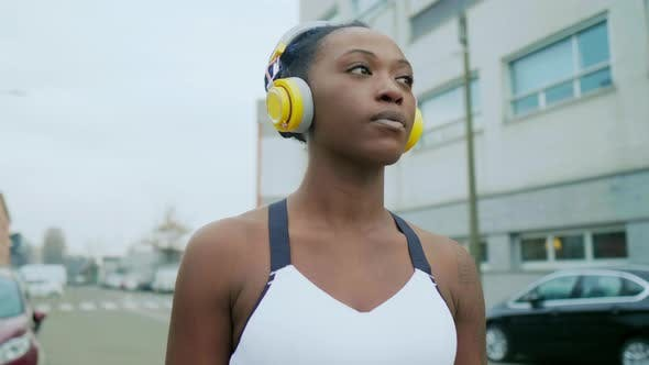 Young woman with headphones in city, Milan, Italy