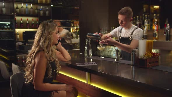 Thumbnail for Bartender Pours Alcohol in Glass, Woman Sits and Talks on Phone at the Bar