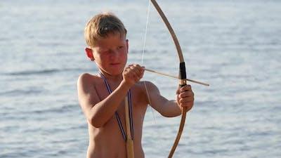 Boy on the Beach is Loading Arrows Into a Bow