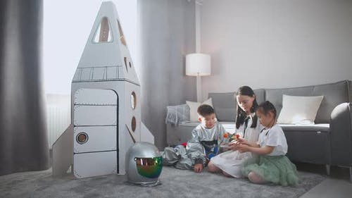 Asian Mother with Kids Play in the Living Room at Home a Boy in an Astronaut Costume Sitting on the