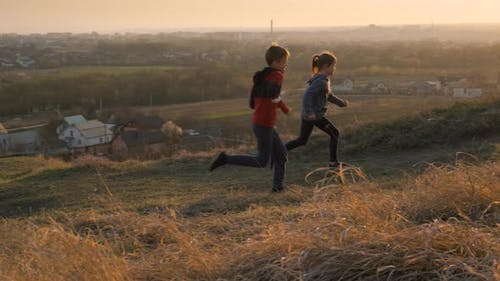 Two children boy and girl running together outdoors on a summer field at sunset