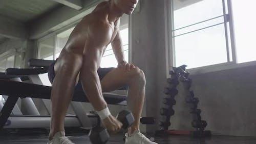 Athletischer Mann macht einige Fitnessübungen in der Sporthalle, Gut aussehender Mann trainiert mit effor
