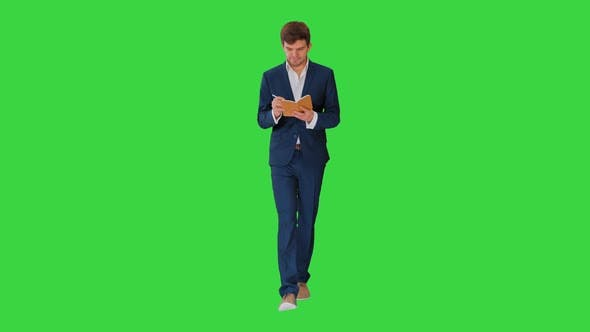 Thumbnail for Young Businessman Thinking and Writing Notes in His Notebook While Walking on a Green Screen Chroma