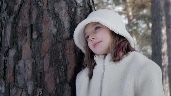 Adorable Pensive Girl Leaning at Tree and Thinking in Winter Forest