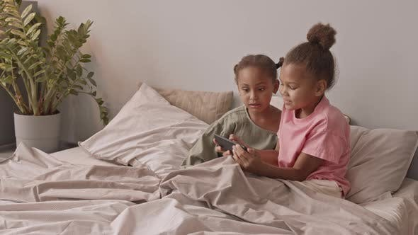 African American Girls Playing Games on Smartphone in Bed