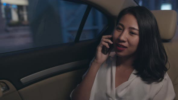 young Asia businesswoman working late talking smart phone in sitting modern city in night.