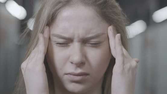 Thumbnail for Headshot of Stressed Young Caucasian Woman Rubbing Temples