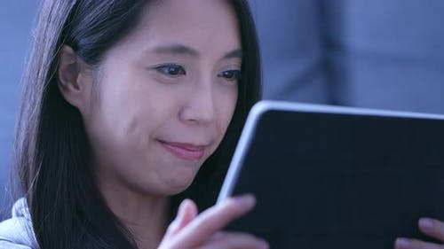 Woman watching drama on tablet computer at home in the evening