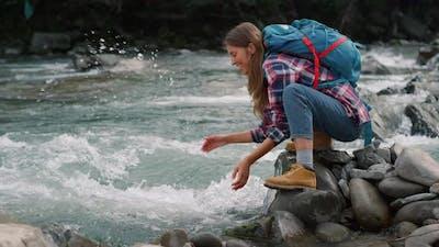Woman Taking Break at River in Mountains