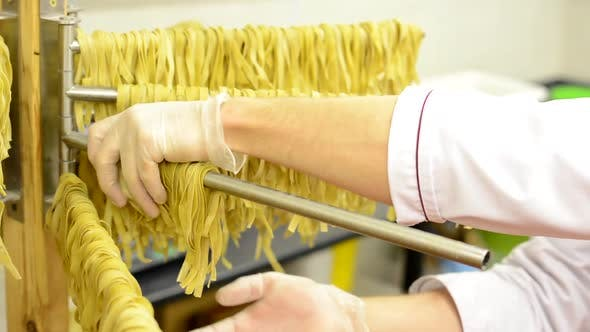 A Worker Takes Down Dried Pasta From Stand - Closeup