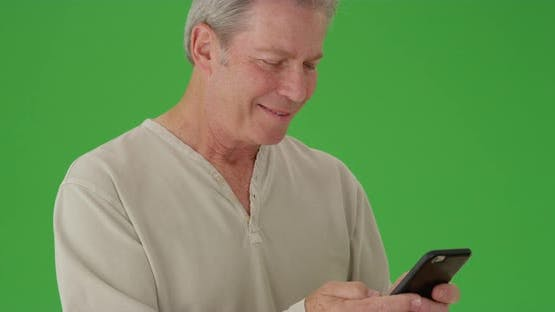 Mature middle aged male reading a cellphone device