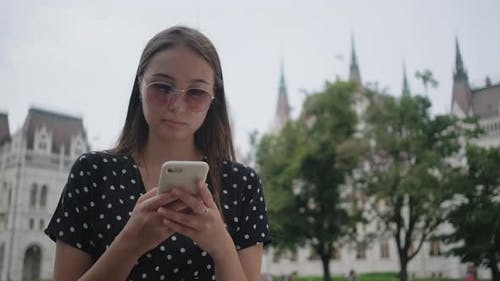 Girl with Cell Near Hungarian Parliament Building in Budapest
