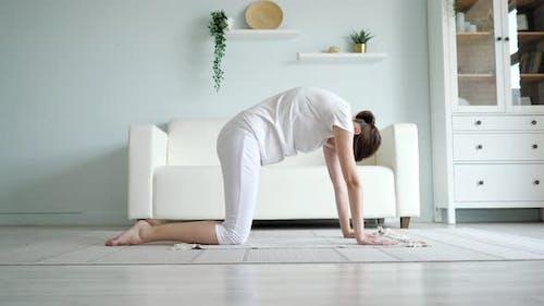Pregnant Lady Does Marjaryasana on Floor Near Sofa at Home