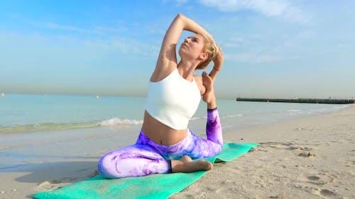Woman Doing Yoga Asana on the Beach