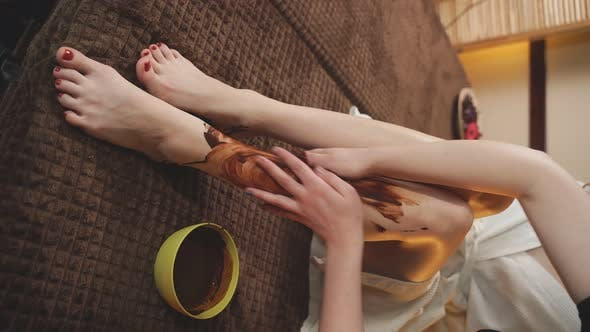 Woman Received Chocolate Applied To Her Feet By a Beautician at a Spa