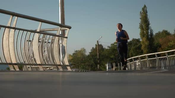 Thumbnail for Young concentrated sportive woman in sports clothes is running on pedestrian bridge at sunrise.